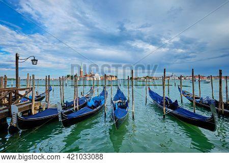 Gondolas in lagoon of Venice near Saint Mark (San Marco) square with San Giorgio di Maggiore church in Venice, Italy