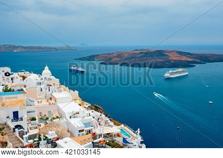 View of Fira Greek town with traditional white houses on Santorini island with cruise ships in sea. Santorini, Greece