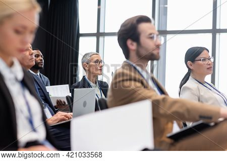 Mature Businesswoman Looking Away Near Multiethnic Colleagues During Seminar.