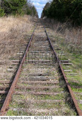 Closeup View Of Rural Railroad Train Tracks Leading Into The Countryside Horizon