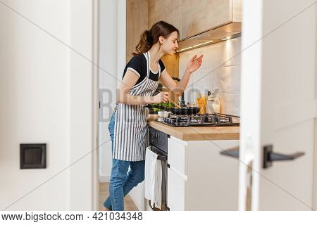 Young Woman In Apron Cooking Healthy Food At Modern Home Kitchen. Preparing Meal With Frying Pan On