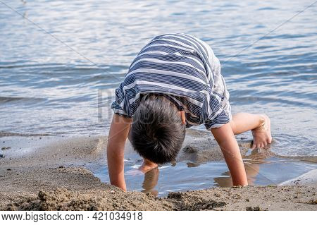 Child Playing Sands Head Down On The Beach. One Little Asian Boy In Casual Clothing Beside Water In
