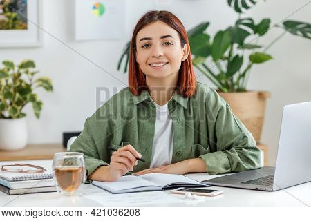 Portrait Of Smiling Young Woman Working At Home With Laptop. Relaxed Businesswoman With Cup Of Tea.