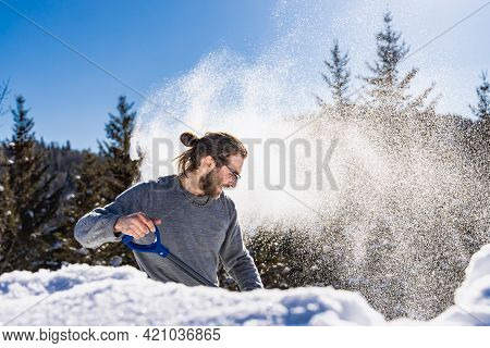 Side View Of A Young Man Energetically Throwing A Heap Of Fresh Snow, Creating A Blizzard, Using A B