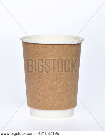 Photo of a disposable brown paper cup on a white background. Photo of a coffee cup made of recyclable materials. Empty paper coffee cup.
