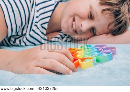 Boy Smiling And Playing With Rainbow Pop It Fidget Toy. Push Bubble Fidget Sensory Toy - Washable An