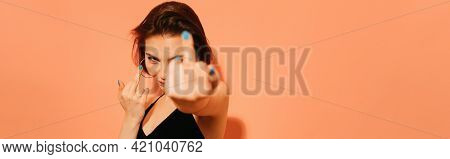 Young Woman With Provocative Middle Fingers Gesture On Orange Background, Banner.