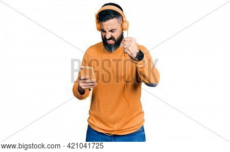 Hispanic man with beard using smartphone wearing headphones annoyed and frustrated shouting with anger, yelling crazy with anger and hand raised