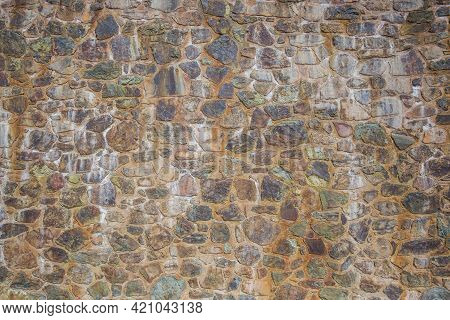 Medieval Cobblestones Wall Made Of Processed Stones In Cement. Antient Architecture Concept. Abstrac
