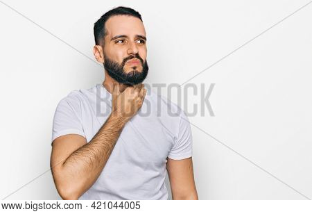 Young man with beard wearing casual white t shirt touching painful neck, sore throat for flu, clod and infection