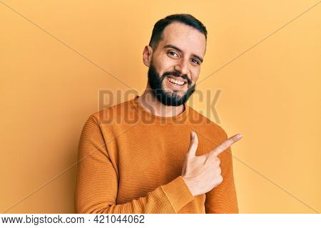 Young man with beard wearing casual winter sweater cheerful with a smile of face pointing with hand and finger up to the side with happy and natural expression on face