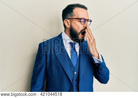 Young man with beard wearing business suit and tie bored yawning tired covering mouth with hand. restless and sleepiness.