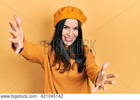 Young brunette woman wearing french look with beret looking at the camera smiling with open arms for hug. cheerful expression embracing happiness.
