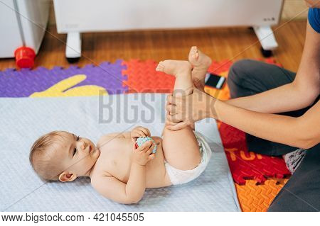 Mom Holds The Baby In A Diaper With A Ball In His Hands By The Legs. Kid Lies On A Bedspread On Top