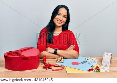 Beautiful hispanic woman with nose piercing doing handcraft creative decoration happy face smiling with crossed arms looking at the camera. positive person.