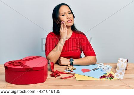 Beautiful hispanic woman with nose piercing doing handcraft creative decoration touching mouth with hand with painful expression because of toothache or dental illness on teeth. dentist