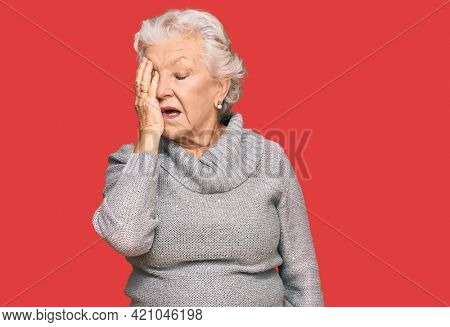 Senior grey-haired woman wearing casual winter sweater yawning tired covering half face, eye and mouth with hand. face hurts in pain.