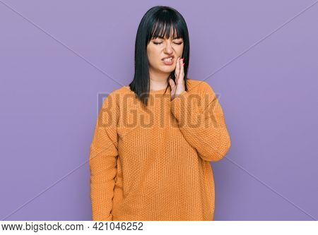 Young hispanic woman wearing casual clothes touching mouth with hand with painful expression because of toothache or dental illness on teeth. dentist