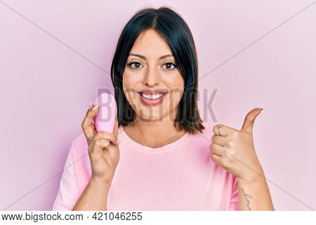 Young hispanic woman using facial exfoliating cleaner smiling happy and positive, thumb up doing excellent and approval sign