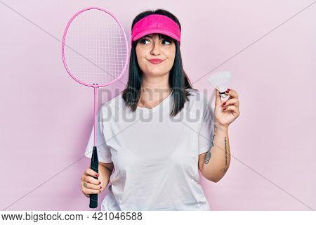 Young hispanic woman holding badminton racket and shuttlecock smiling looking to the side and staring away thinking.