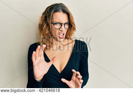 Young caucasian woman wearing business shirt and glasses disgusted expression, displeased and fearful doing disgust face because aversion reaction. with hands raised
