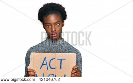 Young african american girl holding act now banner thinking attitude and sober expression looking self confident