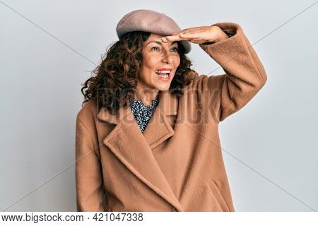 Middle age hispanic woman wearing french look with beret very happy and smiling looking far away with hand over head. searching concept.