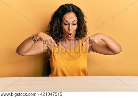 Beautiful middle age woman wearing casual clothes sitting on the table pointing down with fingers showing advertisement, surprised face and open mouth