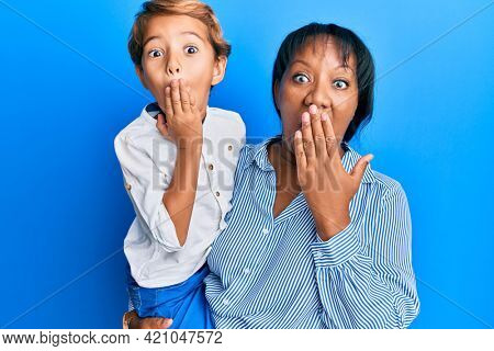 Hispanic family of mother and son hugging together with love covering mouth with hand, shocked and afraid for mistake. surprised expression