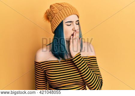 Young modern girl wearing wool hat bored yawning tired covering mouth with hand. restless and sleepiness.