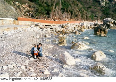 Smiling Dad Squatted Next To A Little Girl, Handing Her Pebbles From A Rocky Beach By The Water Agai