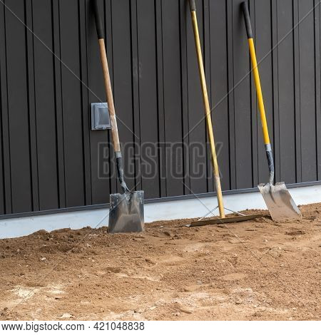 Dirty, Used Shovels And A Rake Stand Upright On The Dirt And Lean Against The Board And Batton Sidin