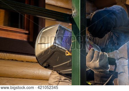 Close Up Of A Young  Man Welder In  Uniform, Welding Mask And Welders Leathers, Weld  Metal  With A