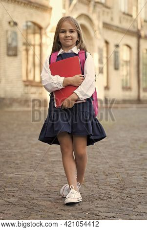 Little Child In Formal Uniform Back To School Carrying Books And Backpack Outdoors, Knowledge Day
