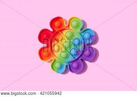 Rainbow Pop It Fidget Toy On Pink Background. Push Bubble Fidget Sensory Toy - Washable And Reusable