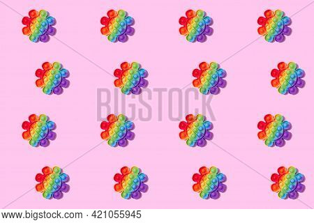 Pattern Made With Rainbow Pop It Fidget Toy On Pink Background. Push Bubble Fidget Sensory Toy - Was