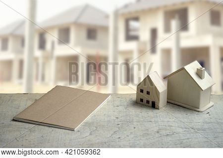 The White Table Had A House Model And A Notebook