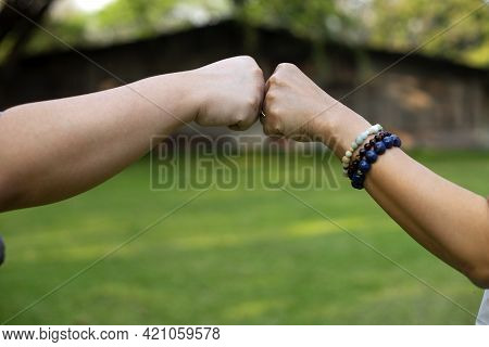 Close Up Image Of Two Hand Fist Bump At The Outdoor Area Green Background To Show Their Feeling Frie