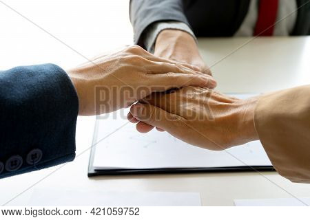Businessmen Stack Their Hands To Show Cooperation