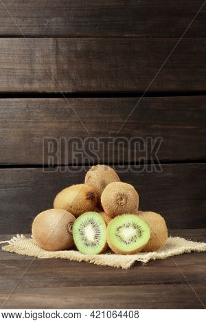 Kiwi On A Wooden Background. A Bunch Of Ripe Kiwi Fruit On A Napkin On A Wooden Background With Copy