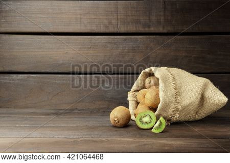 Kiwi On A Wooden Background. Ripe Kiwi Fell From A Bag, On A Wooden Background With Copy Space.