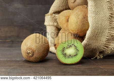 Kiwi On A Wooden Background. Ripe Juicy Kiwi Whole And Halves In A Sack Bag On A Dark Wood Backgroun