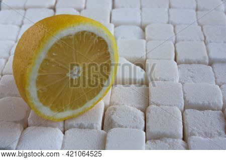 Half A Lemon On The Background Of Large Pieces Of Refined Sugar, The Concept Of Taste Contrast
