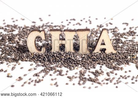 Word Chia Made Of Wooden Letters Standing On Chia Seeds Scattered On A White Table