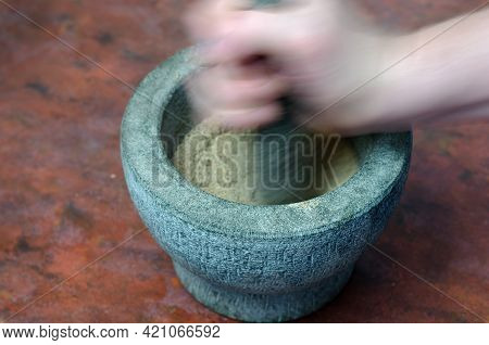 Blurry Motion. A Hand Grinds With A Pestle Spices And Herbs In A Gray Stone Mortar. Granite Mortar W
