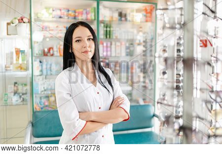 Medicine, Pharmacy And Optics. Portrait Of A Woman Doctor Or Pharmacist In A White Coat. In The Back