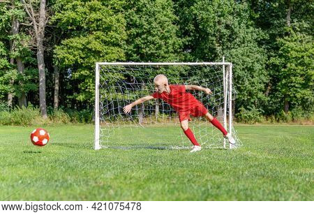 A Young Soccer Player-goalkeeper In A Red Uniform Catches The Ball, Defending The Goal. Children\\\\