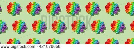 Banner Pattern Made With Rainbow Pop It Fidget Toy On Green Background. Push Bubble Fidget Sensory T