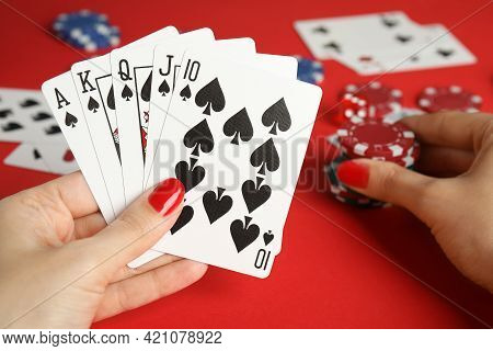 Woman Holding Playing Cards With Royal Flush Combination And Poker Chips At Red Table, Closeup