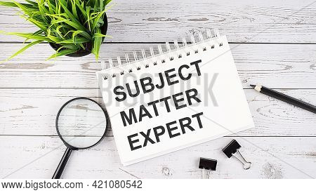 Subject Matter Expert Text Concept Write On Notebook With Office Tools On Wooden Background